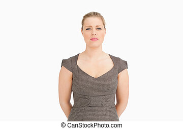Woman standing with her arms behind her back against white...