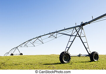 Resting irrigation pivot in a green grass field.