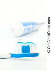 Tooth brush next to a tube of toothpaste