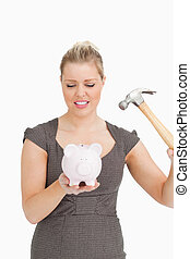 Serious woman with a piggy bank and a hammer against white...