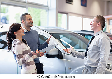Couple chatting with a salesman in a carshop