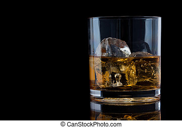Tumbler glass with whiskey against a black background