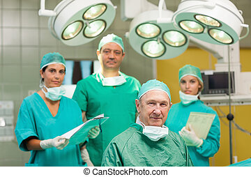 Smiling surgeon sitting with a team behind him in a surgical...