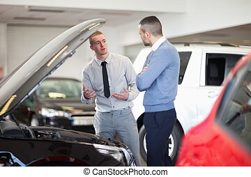 Two men chatting in front of an open engine