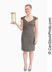 Woman holding a hourglass in her hand against white...