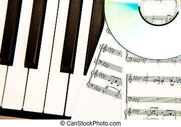 Compact disc and music scores placed on piano