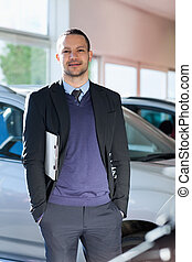Man standing beside a car in a dealership