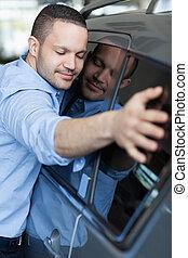 Man hugging a car in a car delaership