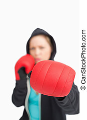 Woman boxing with a red gloves against white background