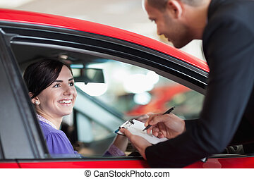 Woman in a car talking with a salesman