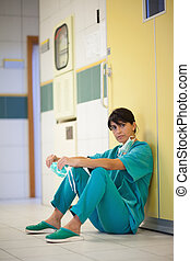 Surgeon sitting on the floor in a hallway