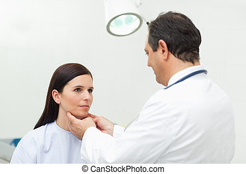 Doctor auscultating the neck of his patient in an...