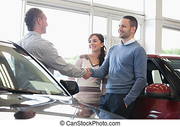 Man shaking a car dealer hand with his wife