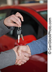 People shaking hands while holding keys in a car shop