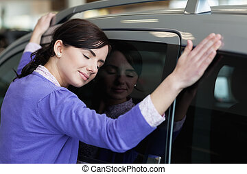 Woman hugging a grey car in a car dealership
