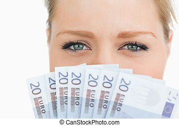 Close up of a woman face hidden with euro banknotes against...