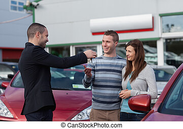 Salesman giving car keys to a couple in a dealership