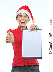 Happy young woman in Christmas hat showing blank clipboard and thumbs up