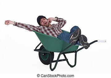 Man dozing in a wheelbarrow