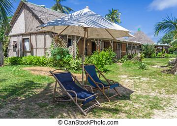 Coastal straw house with deck chairs and parasol in...