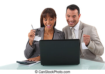 Cheerful business professionals watching a video on their laptop