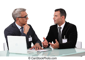 Men chatting at a desk