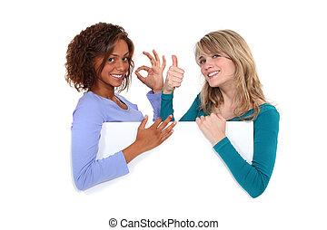 Satisfied girls behind white board