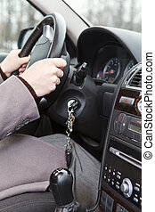 Women hands on steering wheel in land vehicle