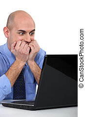 Excited bald man sat at laptop