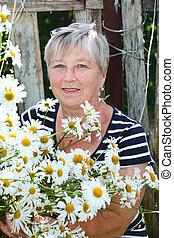 Senior adult female holding growing chamomiles