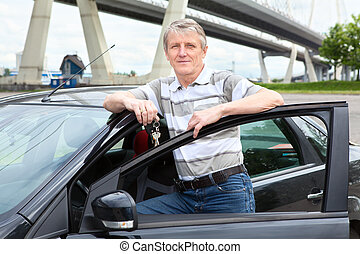 Happy mature driver with car key standing near the land...