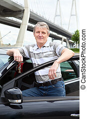 Happy mature driver with ignition key standing near the car