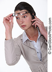 Shocked woman lifting glasses during call