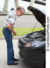 Confused mature driver standing in front of car with opened...