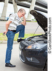 Confused driver standing front of car with opened engine...