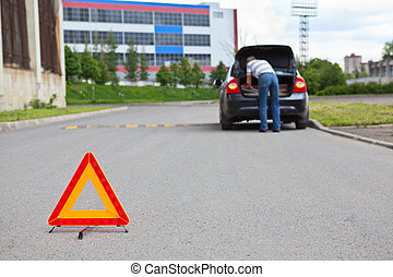 Triangle warning sign on road foreground and driver in car...