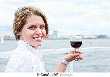 Smiling young woman holding red wine glass in hand