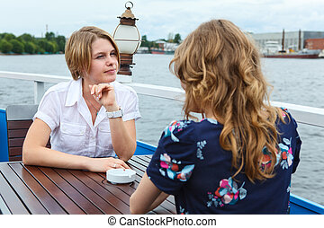 Young woman sitting against girlfriend at cafe table