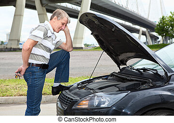 Confused mature driver standing front of car with opened...