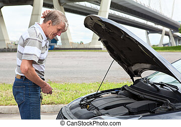 Confused mature driver standing in front of vehicle with...
