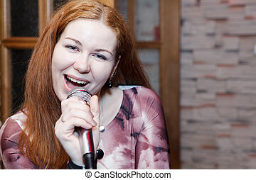 Young woman a singer sings a song with microphone. Copyspace