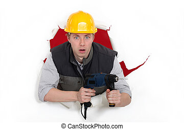 A man popping through the wall with a drill.