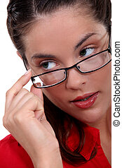 Woman seductively removing glasses