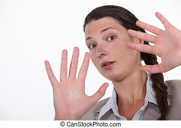 Shocked woman holding hands up