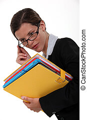 Woman with glasses and folders in hand