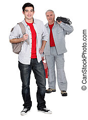 apprentice electrician and senior craftsman standing...