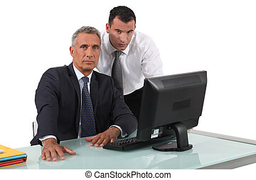 Office workers in front of a desktop computer