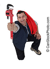 Tradesman holding up a pipe wrench