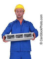 Builder carrying heavy building block