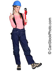 Portrait of a tradeswoman holding a pipe wrench and giving...